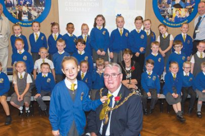 Head girl Talia Sullivan and head boy Joseph Mee presenting the Mayor and Mayoress with the Carr Mill Primary School democracy yellow tie and yellow flowers.