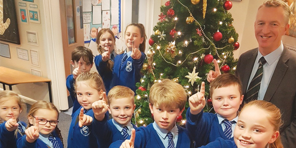 Headteacher Paul Kinsella and members of St Monica's  student council all pointing to signify lots of £1's for R Charity