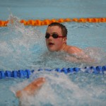 A swimmer heads down the pool